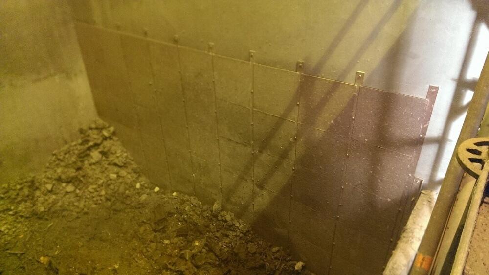 <p>fertig instandgesetzte Bunkerwand mit zusätzlicher Schutzbeplankung aus Stahlplatten</p>